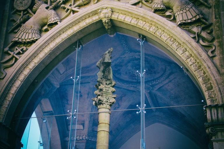 La statua di Sant'Oronzo si rispecchia nella vetrata del Sedile.